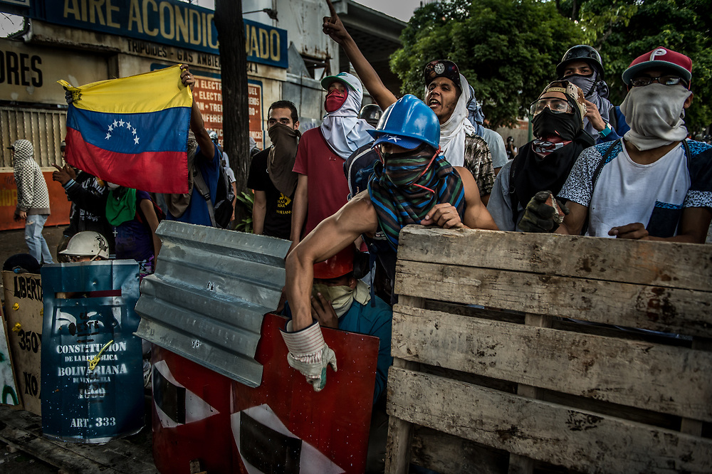 CARACAS, VENEZUELA - JULY 26, 2017: Members of La Resistencia bang on their metal shields to taunt soliders, while taking refuge behind a street barricade that they built during clashes with soldiers during an anti-government protest to demand that the National Constituent Assembly election scheduled for Sunday, July 30th be cancelled. The political opposition called for a 48 hour national strike on July 26th and 27th, and for their supporters to close businesses, not go to work, and instead create barricades to block off their streets.  Opposition controlled areas of the country were completely shut down.  The strike was called as part of the opposition's civil resistance movement - that began on April 1st, to protest against the Socialist government's attempt to elect a new assembly that will have the power to re-write the constitution, and their opposition to the Socialist's continued threats to Venezuelan Democracy.  PHOTO: Meridith Kohut for The New York Times