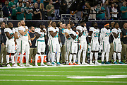 The Miami Dolphins stand along the sideline, many with their hands on their hears, during the playing of the National Anthem before the NFL week 8 regular season football game against the Houston Texans on Thursday, Oct. 25, 2018 in Houston. The Texans won the game 42-23. (©Paul Anthony Spinelli)