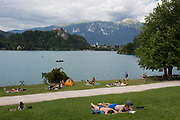 Sunbathers lie along the shore of Lake Bled with Bled castle on the top of cliffs, on 18th June 2018, in Bled, Slovenia.