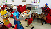 """HARBIN, CHINA - JUNE 07: (CHINA OUT) <br /> <br /> A boy consumer takes over meals from a robot waiter at Liu Hasheng Robot Restaurant on June 7, 2015 in Harbin, Heilongjiang province of China. A Haiying robot manufacturer in north China\'s Harbin Harbin Economic and Technological Development Zone has developed into a comprehensive company where multifunctional robots could be made out to work on the land, in water and air. Liu Hasheng, chief manager and founder of the robot manufacturer, opened the first conprehensive robots restaurant in China with \""""waiters\"""" produced by his own company. According to Liu Hasheng, those robot waiters have been sold out throught out country and his orders has also a great business opportunity in the future.<br /> ©Exclusivepix Media"""