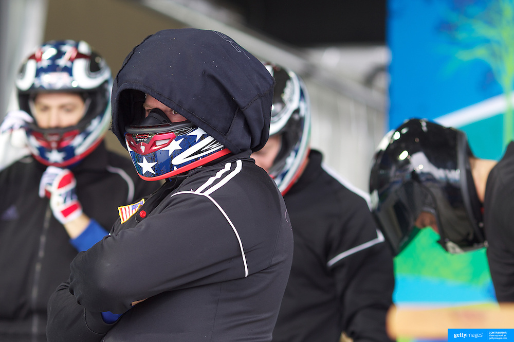 "A USA team prepare themselves in the start area during the Bobsleigh Four-man competition  at The Whistler Sliding Centre, Whistler, during the Vancouver Winter Olympics. 26th February 2010. Photo Tim Clayton..'BOB'..Images from the Four-man Bobsleigh Competition. Winter Olympics, Vancouver 2010..History was made at the Whistler Sliding Centre when the USA four-man bobsleigh team, led by Steven Holcomb took the Gold. The first time since 1948, a gap of 62 years, since the USA have won an Olympic Bobsleigh gold and they did it with their sleigh named ""Night Train""...The four days of practice and competition show the tension, nervousness and preparation as the teams of hardened men cope with the challenge of traveling at average speeds of over 150 km an hour. Indeed, five teams had already pulled out of the event before the opening heats because of track complexity, speed and fear, and on the final day, another four teams did not start after six crashes in the first two heats...Teams warm up behind the start complex, warming muscles in the cold in preparation for the explosive start. Many teams prepare in silence, mentally preparing themselves as they wait at the top of the run, in the bobsleigh sheds and the loading areas for their turn. When it's time to slide each team performs it's own starting ritual, followed by the much practiced start out of the blocks for just over four seconds, the teams are then in the hands of the accomplished drivers as they hurtle down the track for just over fifty seconds...Spectators clamber for the best position on track to see the sleighs for a split second, many unsuccessfully try to capture the moments on camera, The rumble of the sleigh is heard then the crowds gasp as it hurtles past in a blur...The American foursome of  Steven Holcomb, Justin Olsen, Steve Mesler and Curtis Tomasevicz finished with a pooled four-heat time of 3min 24.46sec. The German team led by Andre Lange won the Silver Medal in a combined time of 3min 24.84sec"