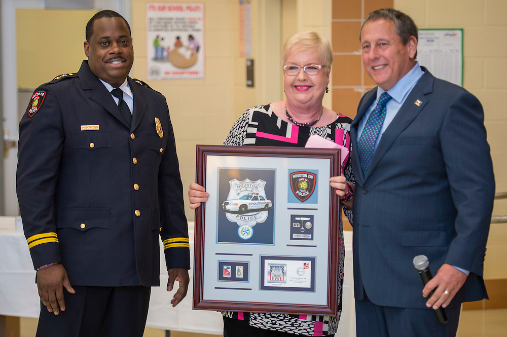 Assistant Chief Michael Benford, left, and Chief Robert Mock, right, honors retired officer Patricia Graveline, center, during the Houston ISD Police awards banquet at Thompson Elementary School, August 15, 2014.
