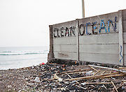 "A wall with a ""Clean Beach"" writing made of flip-flops left over on Canggu Beach. According to a record, around 3,5 million tourists from around the world visited the island for vacation in 2014. Most of them preferred staying in the southern coast such as in Kuta, Nusa Dua, and Sanur. These are the tourism hubs of Bali that naturally attract investors' interest to build hotels and other leisure establishments. The island's tourism is indeed inseparable from its southern coast's history, an area blessed with breathtaking beaches. It is from here the Bali holiday business began to develop as the influx of Australian hippies and surfers to Kuta started back in the 70s. The fishermen's villages would later transform drastically because of it. Hotels, restaurants, and other facilities were growing and spreading along the coast so fast like mushrooms in a rainy season."