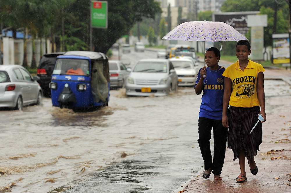 DAR ES SALAAM, TANZANIA -  13-12-03  -  Pedestrians walk along flooded United Nations Road during a rain storm in Dar es Salaam, Tanzania on December 3, 2013. Photo by Daniel Hayduk