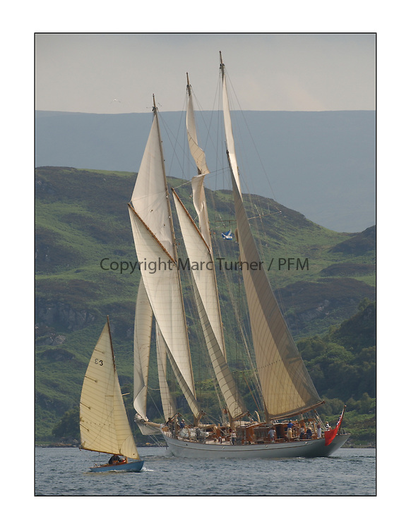 An 1897 Tarbert built Fife, Lotus sails benaeth  the .three masted Schooner Adix...This the largest gathering of classic yachts designed by William Fife returned to their birth place on the Clyde to participate in the 2nd Fife Regatta. 22 Yachts from around the world participated in the event which honoured the skills of Yacht Designer Wm Fife, and his yard in Fairlie, Scotland....Marc Turner / PFM Pictures