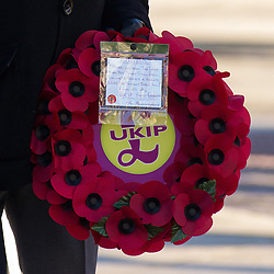 © Licensed to London News Pictures . 10/11/2013 . Bury , UK . A man carrying a UKIP branded poppy wreath prior to laying it at the foot of the First World War monument in Bury town centre during the Remembrance Sunday service on Sunday 10th November 2013 . UKIP are being accused of politicising remembrance by placing brightly branded UKIP poppy wreaths at war memorials during Remembrance Sunday commemorations across the UK on Sunday (10th November 2013) . Remembrance Sunday service at Bury Parish Church , Greater Manchester today (Sunday 10th November 2013) . Photo credit : Joel Goodman/LNP