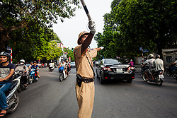 A policeman regulates traffic at a crossroad of Hanoi, Vietnam, Southeast Asia