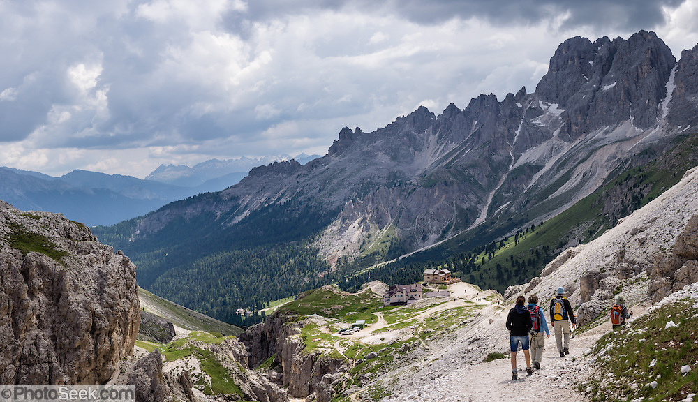 Hike down Vaiolet Valley towards Rifugio Vajolet Hutte and Val di Fassa, in the Rosengarten/Catinaccio Dolomites, Italy, Europe. From Pera di Fassa village (in Pozza di Fassa comune in Val di Fassa), in Trentino-Alto Adige/Südtirol region, Italy, take a bus or lift to visit Rifugio Gardeccia Hutte and hike onwards. 200 million years ago, Triassic coral reefs fossilized into Dolomite. Collision of tectonic plates lifted the Dolomites within the Southern Limestone Alps. UNESCO honored the Dolomites as a natural World Heritage Site in 2009. This panorama was stitched from 4 overlapping photos.
