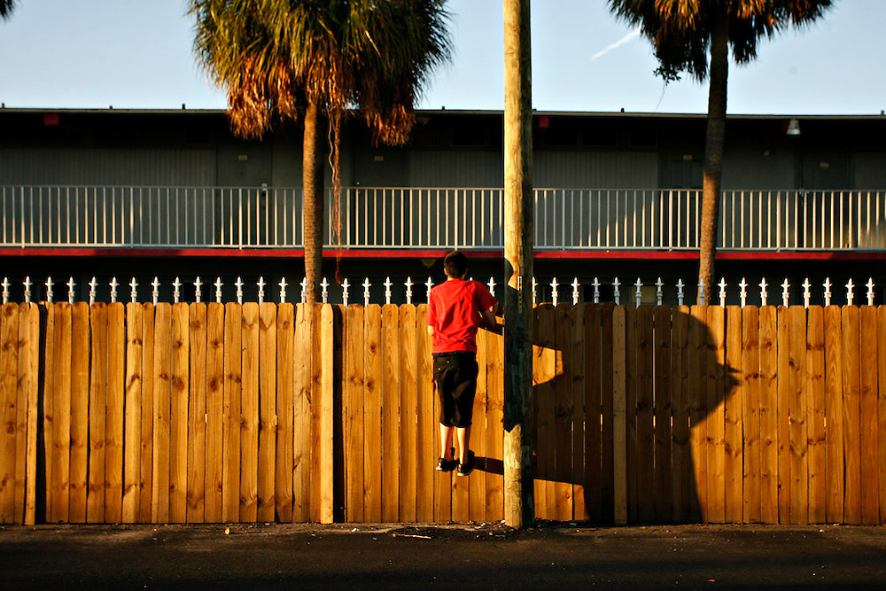 MELISSA LYTTLE   |   Times<br /> SP_345156_LYTT_MOTEL_7 (November 22, 2011, St. Petersburg, FL) Christopher &quot;C.J.&quot; Stone Jr., 15, jumps to see over the privacy fence erected on the northside of the Mosley Motel, and into the parking lot of the neighboring Economy Inn Stadium Motel, where his mom had gone to look for him when he disappeared for a few minutes. As C.J.'s mom tried to re-enter the Mosley, the clerk at the front desk stopped her, saying she was seen on the security camera slipping into the Economy Inn, so it was assumed it was for a drug deal. The Mosley has taken great measures to clean up their act, reduce the number of police calls and to separate themselves from the Economy Inn, where drugs and prostitutes run rampant. [MELISSA LYTTLE, Times]