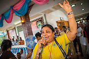 "29 SEPTEMBER 2012 - NAKORN NAYOK, THAILAND:  A woman sings praise and seeks the blessings of Ganesh during observances of Ganesh Ustav at Wat Utthayan Ganesh, a temple dedicated to Ganesh in Nakorn Nayok, about three hours from Bangkok. Many Thai Buddhists incorporate Hindu elements, including worship of Ganesh into their spiritual life. Ganesha Chaturthi also known as Vinayaka Chaturthi, is the Hindu festival celebrated on the day of the re-birth of Lord Ganesha, the son of Shiva and Parvati. The festival, also known as Ganeshotsav (""festival of Ganesha"") is observed in the Hindu calendar month of Bhaadrapada, starting on the the fourth day of the waxing moon. The festival lasts for 10 days, ending on the fourteenth day of the waxing moon. Outside India, it is celebrated widely in Nepal and by Hindus in the United States, Canada, Mauritius, Singapore, Thailand, Cambodia, Burma , Fiji and Trinidad & Tobago.     PHOTO BY JACK KURTZ"