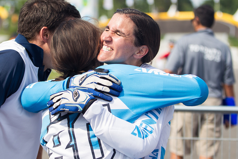Maria Diaz (R) of Argentina gives her sister Mariana Diaz a hug after Mariana won the bronze medal in the BMX competition for the 2015 Pan American Games in Toronto, Canada July 11,  2015.  Maria was 5th in the competition. AFP PHOTO/GEOFF ROBINS