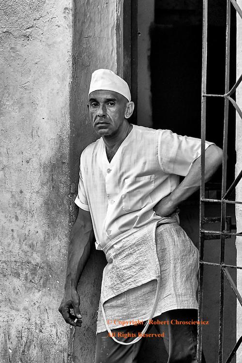 Bakers Break (B&W): A baker takes a morning break, smoking as he leans against a wall, Camagüey Cuba.
