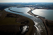 Nederland, Limburg, Gemeente Sittard-Geleen, 07-03-2010; Grevenbicht, de Maas met meander gezien naar het zuiden, de rivier vormt de grens met Belgie (Grensmaas). Midden rechts een grindplas ontstaan door grindwinning, de industrie van DSM in Geleen aan de horizon. .The meandering river with view to the south, the river forms the border with Belgium (Meuse). Middle right a gravel pond created by gravel extraction, industrie of DSM in Geleen in the distance..luchtfoto (toeslag), aerial photo (additional fee required).foto/photo Siebe Swart