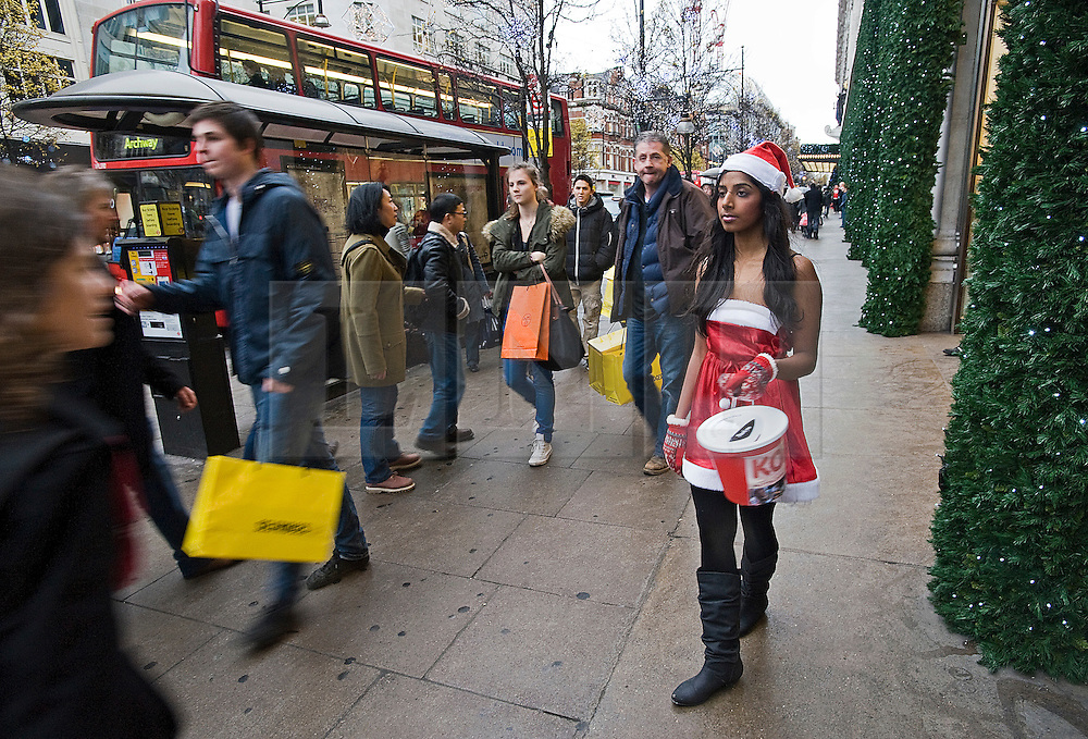 **CAPTION CORRECTION*** © Licensed to London News Pictures. 23/12/2011. London, UK. Shoppers walk past a girl dressed in a santa costume collecting money for charity on Oxford Street, London on December 23, 2011 . £1 million GBP is expected to be spent every minute on what is the busiest shopping day of the year. Photo credit: Ben Cawthra/LNP