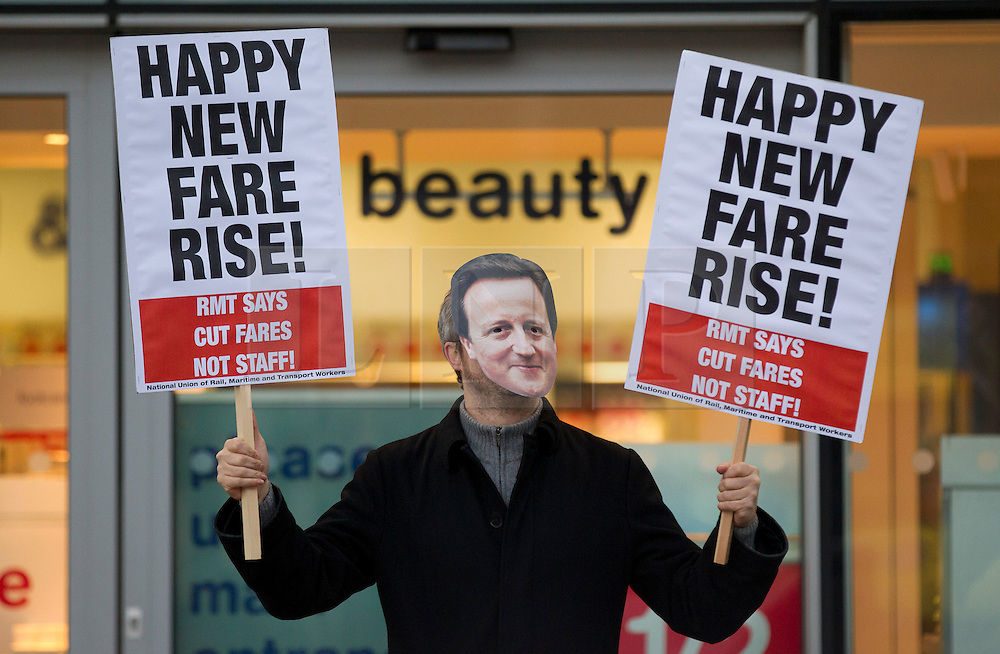 © Licensed to London News Pictures. 02/01/2014. London, UK. A union supporter is seen protesting over today's (02/01/2014) 3.1% rail fare rise outside King's Cross Station in London this morning. The rail fare rise came in to force today as most across the country returned to work for the start of 2014. Photo credit: Matt Cetti-Roberts/LNP