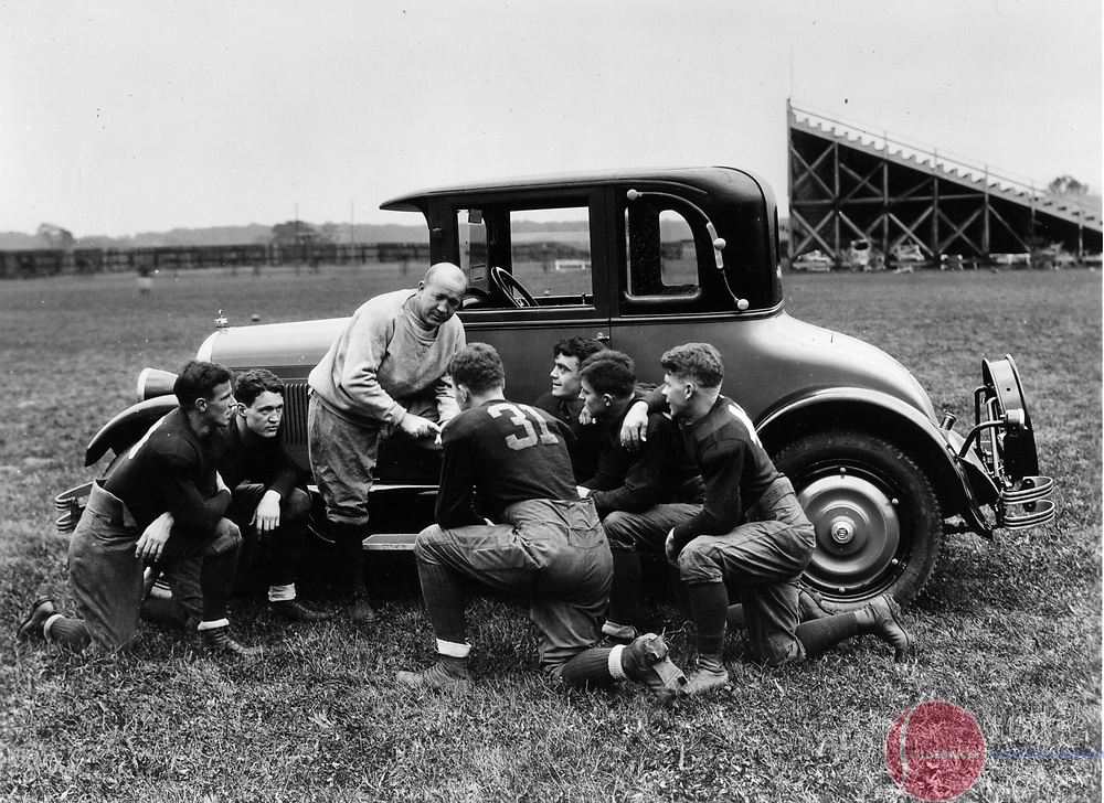 Knute Rockne addresses football players with a 1927 Studebaker Dictator.