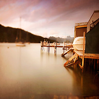 a row of boatsheds at sunset with mountains in the background