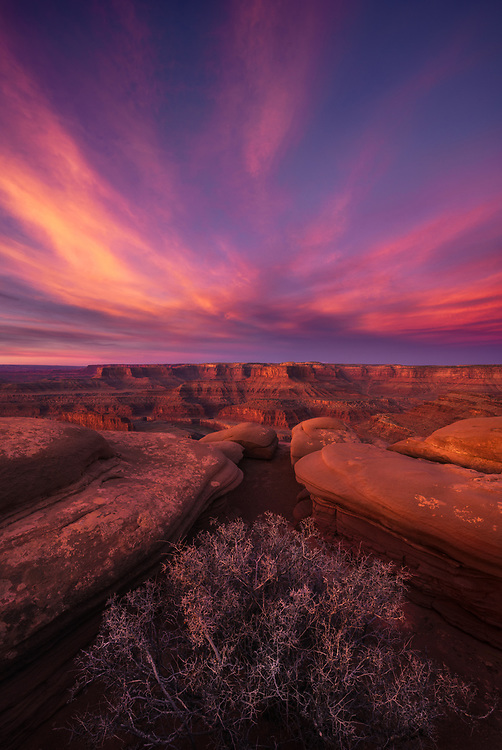 Dramatic sunrise clouds light up the desert landscape as seen from Dead Horse Point State Park in Utah, USA.