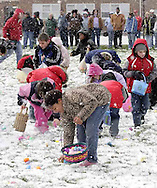 Kelsey Hoskins, 8 (in front) fills her basket as snow fills the air during an Easter egg hunt sponsored by the Montgomery County Sheriff's Office Police Athletic League, Saturday morning.  A mix of sunshine and snow showers made for an interesting day..