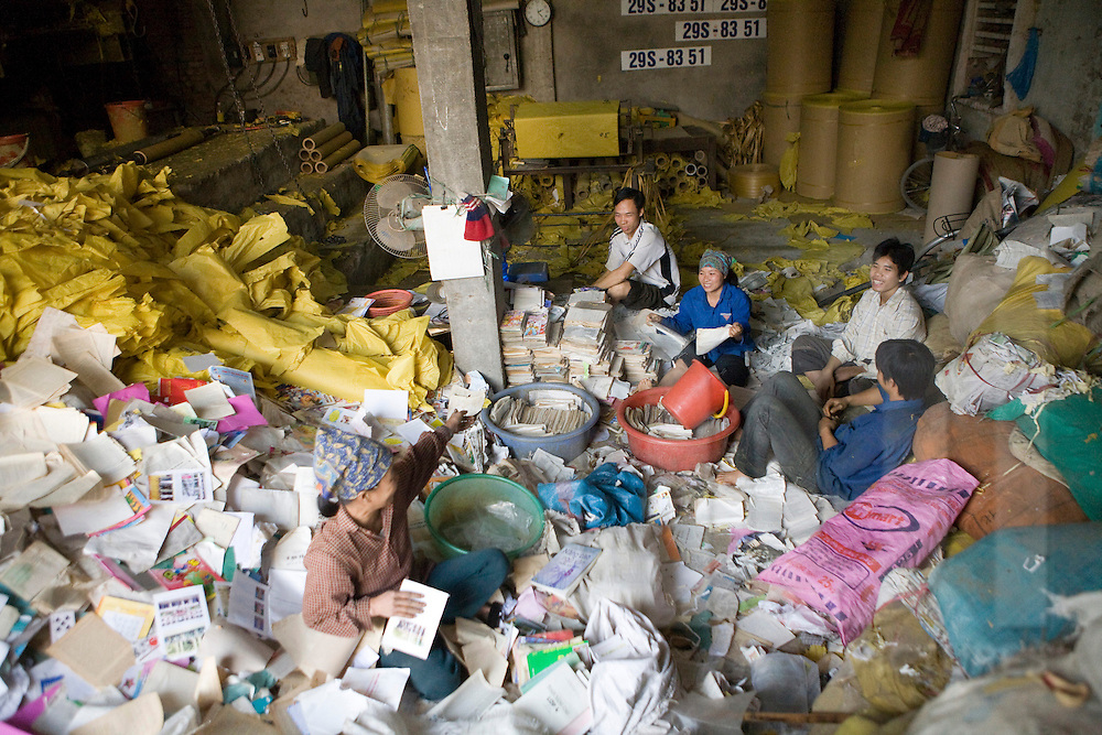 Color film photograph of Vietnamese workers sorting through paper waste in Duong O, a traditional paper recycling village, Bac Ninh Province, Hanoi outskirts, Vietnam, Southeast Asia