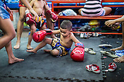23 DECEMBER 2014 - BANGKOK, THAILAND: A boy lands on the floor after sparring in the Kanisorn gym in Bangkok. The Kanisorn boxing gym is a small gym along the Wong Wian Yai - Samut Sakhon train tracks. Young people from the nearby communities come to the gym to learn Thai boxing. Muay Thai (Muai Thai) is a mixed martial art developed in Thailand. Muay Thai became widespread internationally in the twentieth century, when Thai boxers defeated other well known boxers. A professional league is governed by the World Muay Thai Council. Muay Thai is frequently seen as a way out of poverty for young Thais. Muay Thai professionals and champions are often celebrities in Thailand.     PHOTO BY JACK KURTZ