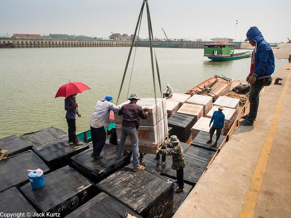 21 APRIL 2014 - CHIANG SAEN, CHIANG RAI, THAILAND: A shipment of computer parts made in Thailand is loaded onto a Laotian flagged river boat for shipment to China in the commercial port in Chiang Saen, Thailand. Water levels in the port are at near record lows. Normally the water is near the top of the concrete wall, but currently it's almost 15 feet below that. Chiang Rai province in northern Thailand is facing a drought this year. The 2014 drought has been brought on by lower than normal dry season rains. At the same time, closing dams in Yunnan province of China has caused the level of the Mekong River to drop suddenly exposing rocks and sandbars in the normally navigable Mekong River. Changes in the Mekong's levels means commercial shipping can't progress past Chiang Saen. Dozens of ships are tied up in the port area along the city's waterfront.      PHOTO BY JACK KURTZ