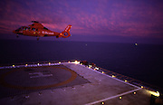 An Aerospatiale SA365N Dauphin II offshore helicopter (reg number G-BKXD) operated by Bond Helicopters takes-off from a gas platform in the Irish Sea bound for its base at Blackpool, England. On duty ferrying offshore gas workers from Morcambe Bay, England, the helicopter flies off into a pink sky as darkness approaches. Left behind are the lights that illuminate the deck of the gas rig, the letter H beneath the facilities' netting. Bond Offshore Helicopters are a British Helicopter operator, specialising in providing offshore helicopter transportation services between Aberdeen, Scotland, Blackpool, Norwich and Humberside to North Sea and Irish Sea oil and gas platforms.