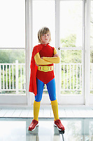 Portrait of young boy (7-9) in superhero costume indoors