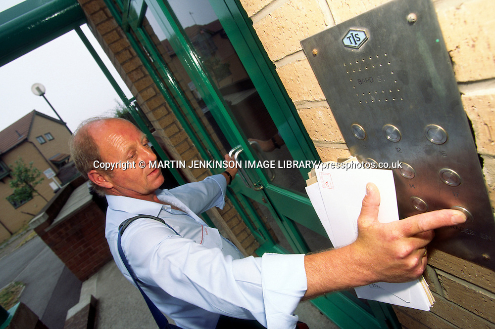 Postman uses an intercom to access a block of flats whilst delivering mail on his walk.