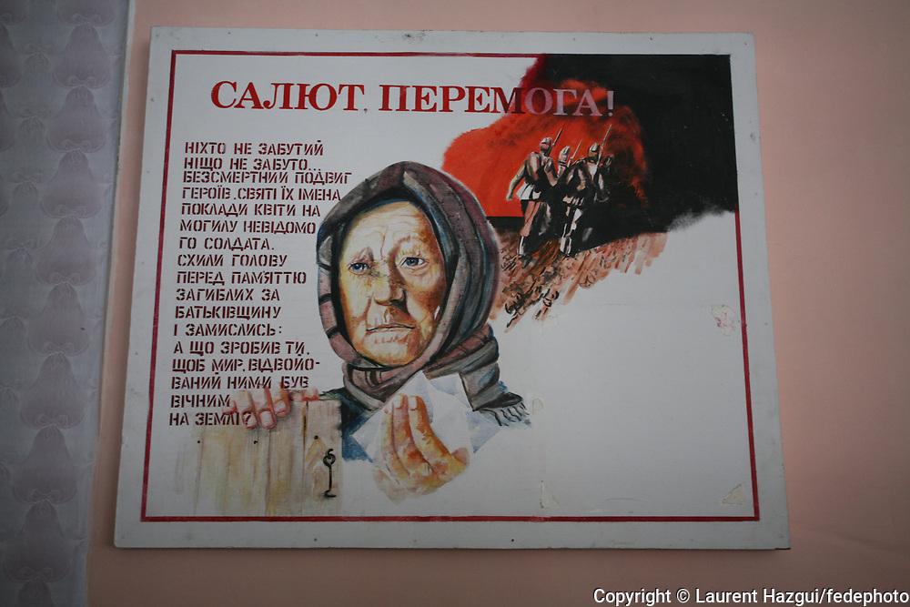 """Ecole de Lugoviki, dirigée par Lidia Olexiivna Bernikova, à quelques km de la zone interdite. Tous les enfants viennent de la région; Ils ont entre 3 et 17 ans. Les enfants ont été les grandes victimes de la catastrophe, plus sensibles qu'ils sont face à la radiation. Les classes sont composées de moins de 10 enfants contre 25/30 il y a 20 ans. Un panneau en l'honneur de pompiers héros morts, ayant fréquenté l'école, lors de la """"liquidation"""" est accroché dans un couloir."""