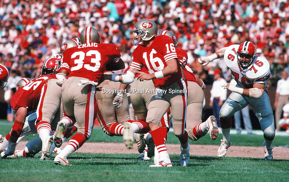 San Francisco 49ers quarterback Joe Montana (16) hands off the ball on a running play to San Francisco 49ers running back Roger Craig (33) during the NFL football game against the Atlanta Falcons on Sept. 18, 1988 in Anaheim, Calif. The Falcons won the game 34-17. (©Paul Anthony Spinelli)