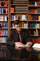 Man wearing suit writing at desk in library