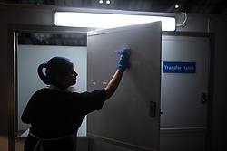 © Licensed to London News Pictures . 23/04/2020. Manchester, UK. VICKY ARMITT (37) cleans the transfer hatch ahead of passing lunch for patients in to ward 7 of the hospital . Vicky , who normally works as cabin crew for Tui , originally volunteered to help whilst furloughed , but was put on staff by the hospital . The National Health Service has built a 648 bed field hospital for the treatment of Covid-19 patients , at the historical railway station terminus which now forms the main hall of the Manchester Central Convention Centre . The facility is treating patients from across the North West of England , providing them with general medical care and oxygen therapy after discharge from Intensive Care Units . Photo credit : Joel Goodman/LNP