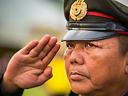 02 DECEMBER 2014 - BANGKOK, THAILAND: A Thai police officer salutes at the end of the Trooping of the Colors parade on Sanam Luang in Bangkok. The Thai Royal Guards parade, also known as Trooping of the Colors, occurs every December 2 in celebration of the birthday of Bhumibol Adulyadej, the King of Thailand. The Royal Guards of the Royal Thai Armed Forces perform a military parade and pledge loyalty to the monarch. Historically, the venue has been the Royal Plaza in front of the Dusit Palace and the Ananta Samakhom Throne Hall. This year it was held on Sanam Luang in front of the Grand Palace.    PHOTO BY JACK KURTZ