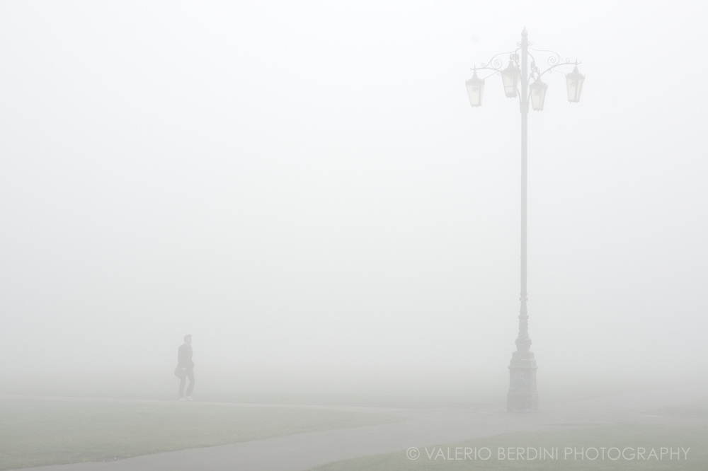 A man walking through the fog approaches 'reality checkpoint', the colloquial name to the lamp post at the intersection of the two paths crossing Parker's Piece in Cambridge, England.