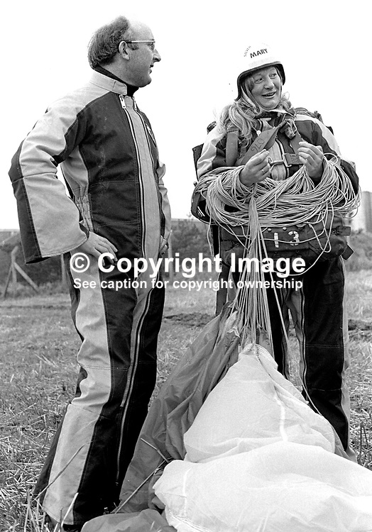Mary Peters, N Ireland, Olympic Gold Medallist, women's pentathlon, back on terra firma following her first ever parachute jump from 2000 ft over Newtownards Airport, Co Down, N Ireland. 26h November 1974. With her in the photo is Colin Wallace, Ministry of Defence employee at British Army HQ, Thiepval Barracks, Lisburn.197411260667a<br /> <br /> Copyright Image from Victor Patterson, 54 Dorchester Park, Belfast, UK, BT9 6RJ<br /> <br /> t1: +44 28 9066 1296<br /> t2: +44 28 9002 2446<br /> m: +44 7802 353836<br /> <br /> e1: victorpatterson@me.com<br /> e2: victorpatterson@gmail.com<br /> <br /> www.victorpatterson.com<br /> <br /> IMPORTANT: Please see my Terms and Conditions of Use at www.victorpatterson.com