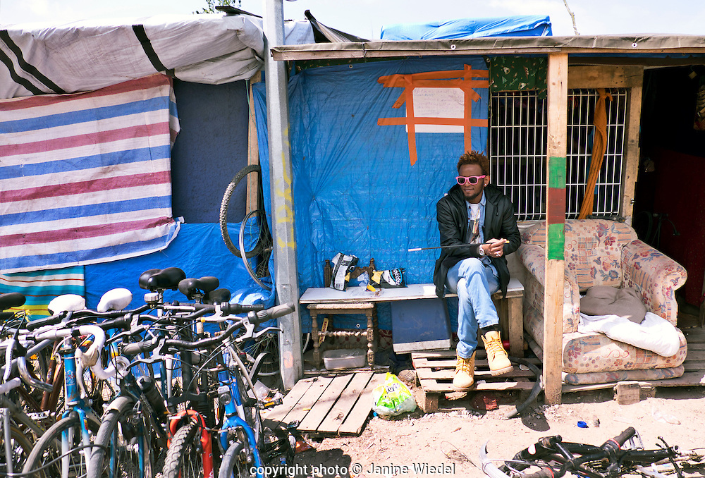 Ethiopian refugee fixing providing people with refurbished bicycles. The Calais Jungle Refugee and Migrant Camp in France