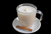 instant chai a cup of hot milk with teabag and cinamon On black Background