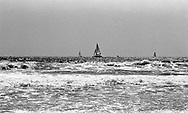 A silver gelatin, black and white, film photograph taken from Venice Beach, California, overlooking the sea, ocean waves, and navigating sailboats during the day.