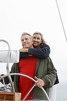 Couple at helm of sailboat, smiling