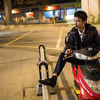 China, Sichuan Province, Chengdu, Young man sitting on motor scooter beneath highway overpass on autumn evening