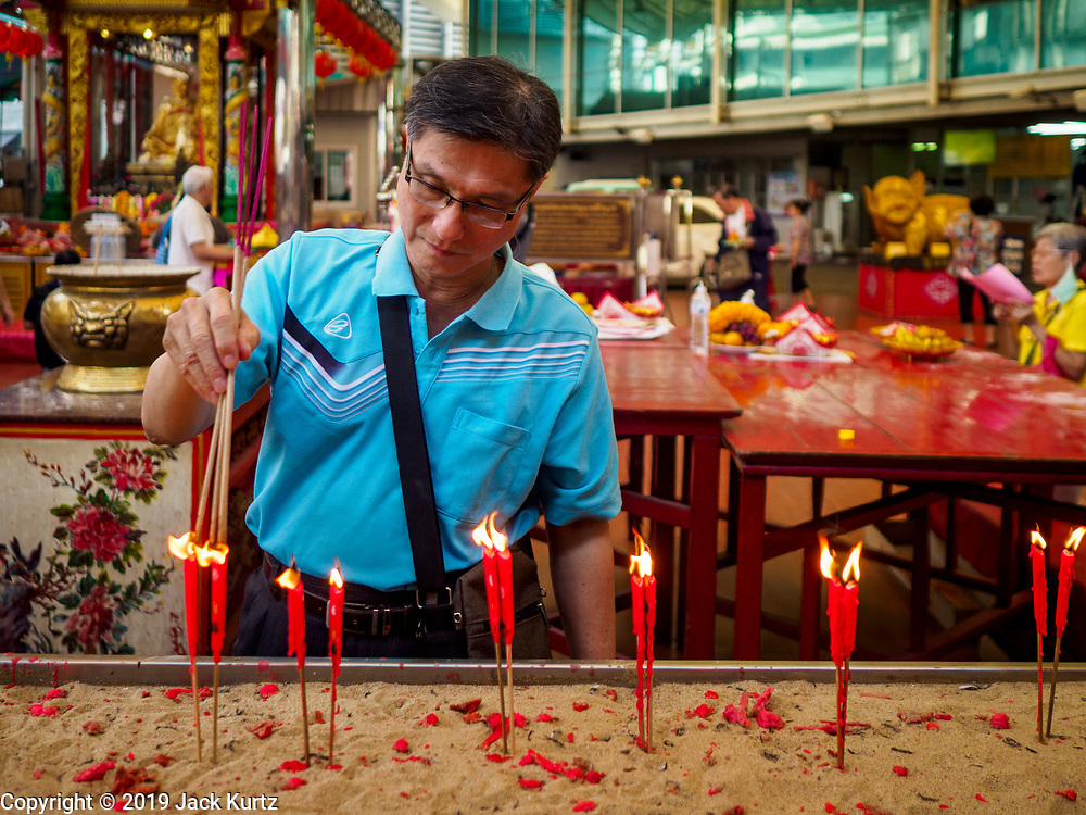 29 JANUARY 2019 - BANGKOK, THAILAND:       A man lights incense before praying the Poh Teck Tung shrine in Bangkok's Chinatown. Chinese temples in Bangkok are getting crowded at people come to the temples to pray ahead of the Lunar New Year. Chinese New Year celebrations in Bangkok start on February 4, 2019. The coming year will be the Year of the Pig in the Chinese zodiac. About 14% of Thais are of Chinese ancestry and Lunar New Year, also called Chinese New Year or Tet is widely celebrated in Chinese communities in Thailand.   PHOTO BY JACK KURTZ