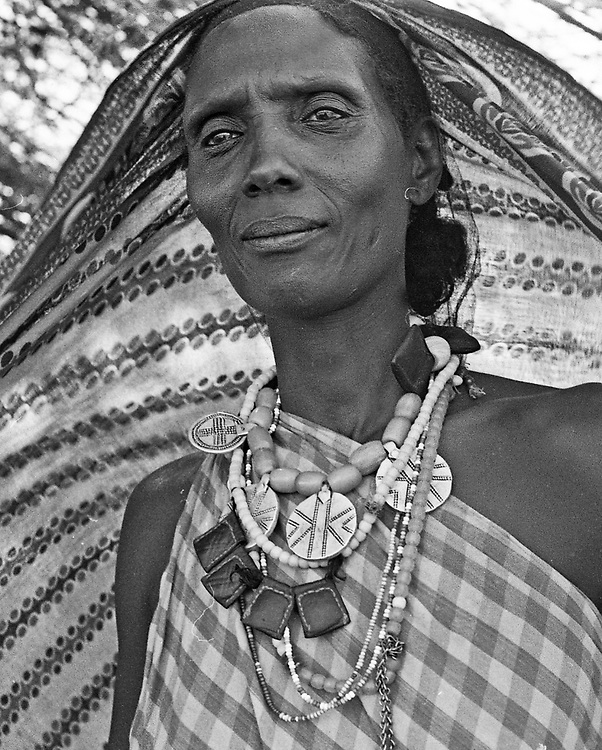 Kenya nomadic woman dressed in traditional cloth and necklace medallions and beads.