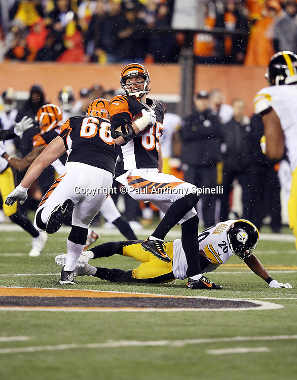 Cincinnati Bengals tight end Tyler Eifert (85) does a pirouette while avoiding a diving tackle attempt by Pittsburgh Steelers strong safety Will Allen (20) as Cincinnati Bengals guard Kevin Zeitler (68) blocks on a pass reception during the NFL AFC Wild Card playoff football game against the Pittsburgh Steelers on Saturday, Jan. 9, 2016 in Cincinnati. The Steelers won the game 18-16. (©Paul Anthony Spinelli)