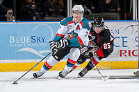 KELOWNA, CANADA -FEBRUARY 25: Damon Severson #7 of the Kelowna Rockets skates with the puck behind the net as Tate Olson #25 of the Prince George Cougars checks him during third period on February 25, 2014 at Prospera Place in Kelowna, British Columbia, Canada.   (Photo by Marissa Baecker/Getty Images)  *** Local Caption *** Damon Severson; Tate Olson;