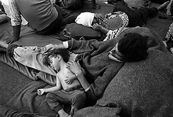 On the border between Kosovo and Macedonia an Ashkali (Roma) father and son sleep soundly, it?s their 5th day waiting to leave Kosovo and cross into Macedonia. The Macedonian government were refusing to let them in. A few days later with UNHCR pressure the group of 500 were allowed to enter...Border Kosovo/Macedonia 1999..