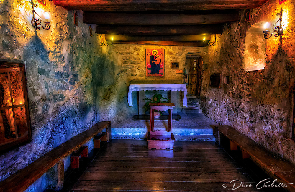 &ldquo;San Francesco enjoys Mass at the Convent of cells in Cortona&rdquo;&hellip;<br /> <br /> In the year 1211, St. Francis and a few of his followers built the first nine cells of the now Franciscan Hermitage, and it has been called Le Celle ever since. Originally, only a few small hermit&rsquo;s cottages and peasant dwellings existed, including a small chapel built during the Lombard invasions and dedicated to the Archangel Michael.  This is believed to be the place where, in May 1226, four months before his death, St. Francis dictated his Will. Following the death of Saint Francis that same year, Brother Elias of Cortona who was among the first to join St. Francis of Assisi in his newly founded Order of Friars Minor, withdrew permanently to the Le Celle Hermitage.  In 1239, Elias carried out a number of improvements and restoration works which ensured the hermitage became a permanent Franciscan property. Brother Elias is in fact considered responsible for having broken up the stone of the caves and created a chapel that was formerly used as a dormitory by the monks, and the small cell where St. Francis lived. I found Le Celle to be one of the pleasant surprises in and around Cortona.  The tiny cells built into the side of the mountain with a stream descending along the structural edge, creates a surreal and picturesque vision of Saint Francis&rsquo; image of God and nature. Imagine the spiritual solitude as Saint Francis would take hermitage here for days of ecstatic meditation with only a loaf of bread, listening to his beloved waterfall beneath a small window.  This image is of the tiny chapel built into the rock of the cliffside. Notice the statue of Saint Francis in the window quietly observing the Mass.