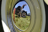 Westbury, New York, USA. June 12, 2016.  A yellow 1948 Bantam Roadster, owned by Wade Jacobs of Mineola, has reflection of man walking by nearby vintage black car on its hubcap, at the Antique and Collectible Auto Show at the 50th Annual Spring Meet at Old Westbury Gardens, in the Gold Coast of Long Island, and sponsored by Greater New York Region, GNYR, Antique Automobile Club of America, AACA. Participating vehicles in the judged show included hundreds of domestic and foreign, antique, classic, collectible, and modern cars.