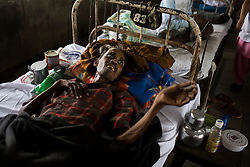 A patient at the Group of TB Hospitals in Mumbai lays on his bed.  Later that day the patient was moved to a different bed where he could receive oxygen.  He died early the next morning.
