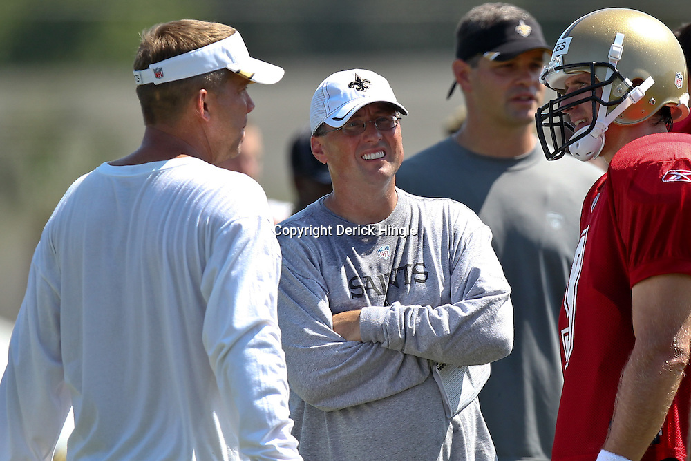 July 31, 2011; Metairie, LA, USA; New Orleans Saints head coach Sean Payton talks with offensive coordinator Pete Carmichael Jr. and quarterback Drew Brees (9) during training camp practice at the New Orleans Saints practice facility. Mandatory Credit: Derick E. Hingle